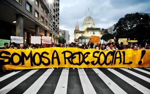 Na Av. Rio Branco, Rio de Janeiro, faixa de manifestantes evidenciando a imbricação entre os espaços físico e digital.