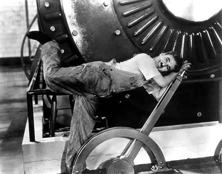 Chaplin e a ironia da rotina industrial (Fonte: https://upload.wikimedia.org/wikipedia/commons/f/f7/Chaplin_-_Modern_Times.jpg)