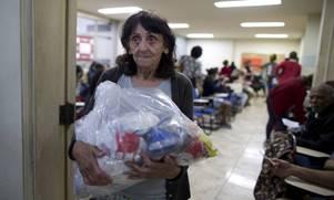 Servidora pública recebe cesta básica do MUSPE Disponível em: https://oglobo.globo.com/rio/saiba-como-doar-alimentos-para-as-cestas-basicas-dos-servidores-do-estado-21603043. Acesso: 10/06/18