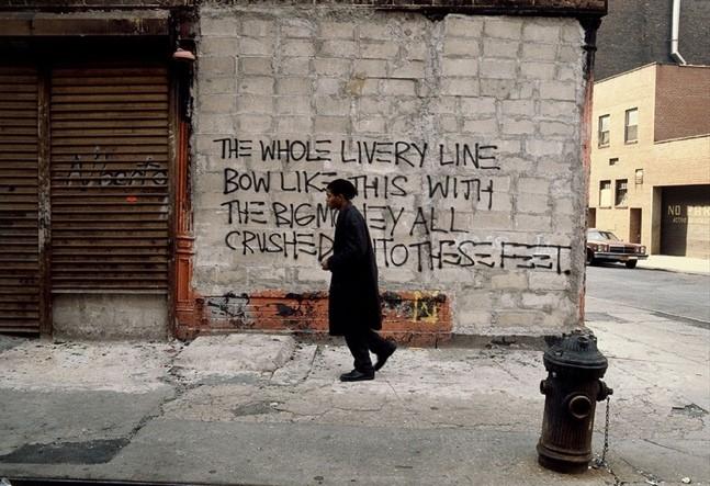 Figura 1: Basquiat em ação no centro de Nova York em 1981. Fotografia de Edo Bertoglio. Disponível em: https://saopaulosao.com.br/conteudos/recomendados/3473-retrospectiva-de-jean-michel-basquiat-1960-1988-com-80-obras-chega-ao-brasil-pela-primeira-vez.html#.